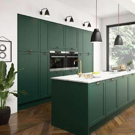 14. Cozinha planejada com ilha verde decorada com pendentes pretos – Foto: Hunker