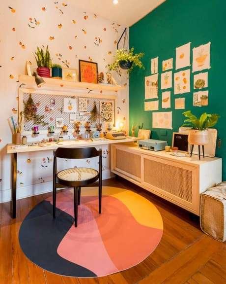 30. Home office simples decorado com tapete redondo colorido e parede verde esmeralda – Foto: Criss Passos