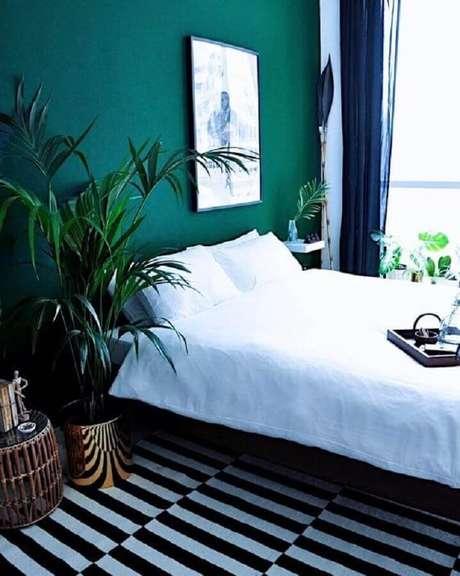 36. Tinta verde esmeralda para parede de quarto de casal simples com vaso de planta grande – Foto: Femme Nouveau