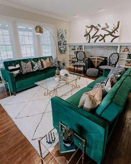 41. Sala branca decorada com mesa de centro de vidro e sofá verde esmeralda com várias almofadas – Foto: Archilovers