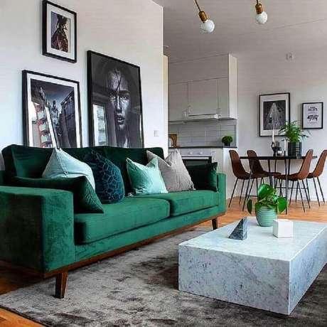44. Sofá verde esmeralda para decoração de sala com tapete cinza e quadros grandes – Foto: Essência Móveis de Design