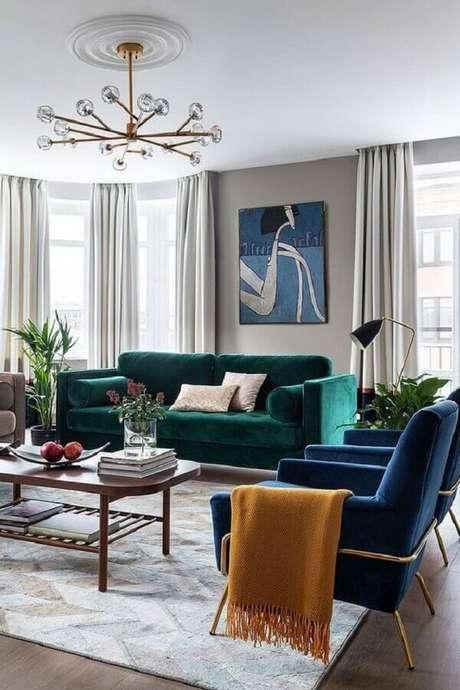 53. Sofá verde esmeralda para sala decorada com poltronas azuis modernas – Foto: Behance