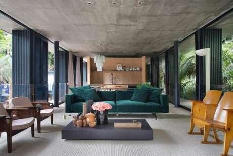 62. Sofá verde para varanda ampla e moderna decorada com poltronas de madeira – Foto: BC Arquitetos