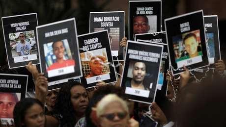Jovens são as principais alvos de homicídio no país; acima, moradores do Rio levantam cartazes de vítimas da violência em protesto no ano passado