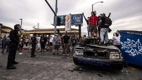 Manifestantes no topo de um carro da polícia queimado em Los Angeles, Califórnia