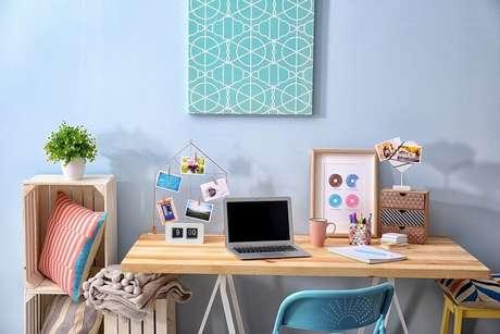 2. Home office com parede azul, objetos decorativos e vasinho de planta – Fonte: Shutterstock