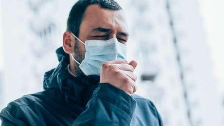 Pessoa com máscara espirrando.