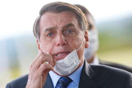 Jair Bolsonaro ajusta máscara ao sair do Palácio do Alvorada, em maio. REUTERS/Adriano Machado