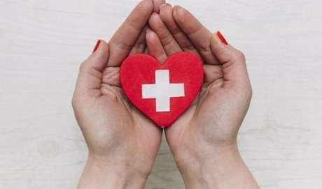 Pessoa segurando com as duas mãos um coração de madeira, com um sinal de adição no meio