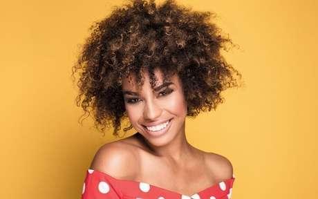 Mulher negra sorrindo em um fundo laranja