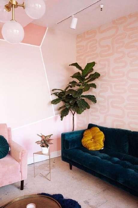 41. Papel de parede rosa pastel para sala de estar decorada com sofá azul marinho e vaso de planta grande – Foto: The Design Files