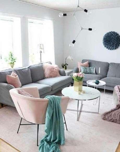 42. Poltrona e almofadas rosa pastel para decoração de sala de estar moderna com sofá cinza – Foto: Revista VD