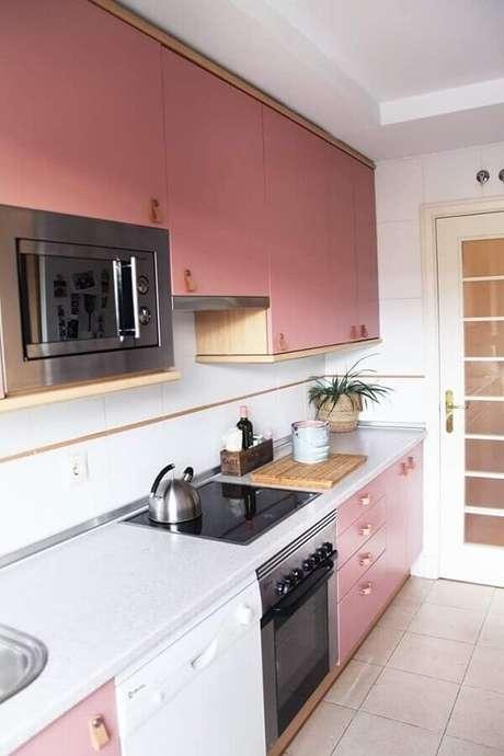 53. Rosa tom pastel para armário de cozinha planejado com detalhes em madeira – Foto: Pinterest