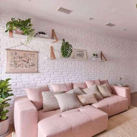 54. Sala branca decorada com sofá rosa pastel e parede de tijolinho – Foto: Pinterest