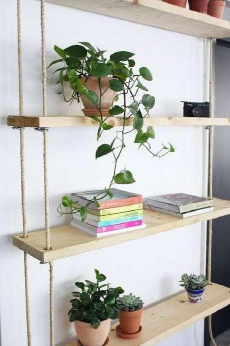 13. Prateleira de madeira suspensa por corda decorada com vasos de plantas e livros – Foto: Ligia Batschke