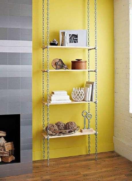21. Parede amarela decorada com prateleira suspensa com correntes – Foto: Pinterest