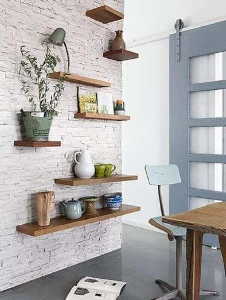 22. Decoração simples para ambiente com parede de tijolinho branco e prateleiras suspensas de madeira – Foto: Casa de Valentina