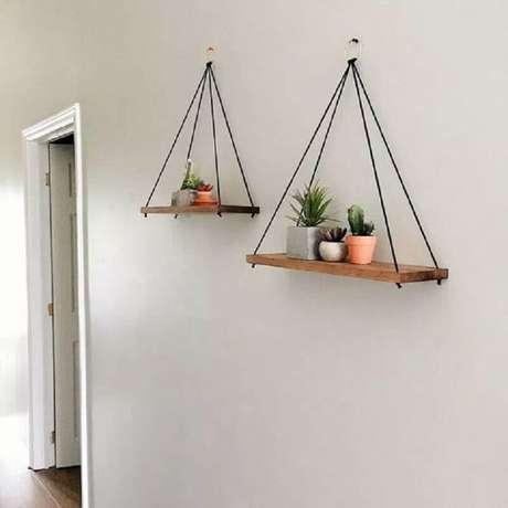 27. Modelo de prateleira suspensa de madeira para decoração minimalista – Foto: Viajando no Apê