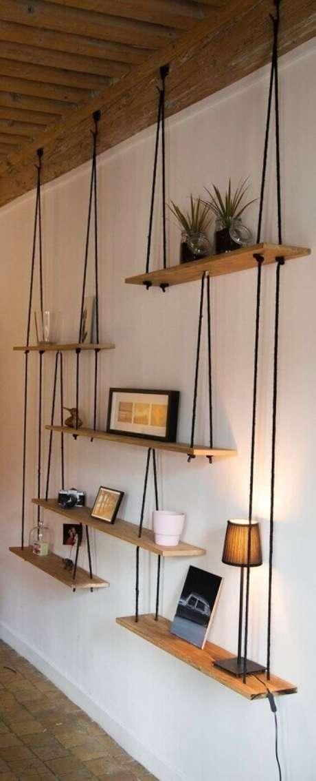 33. Parede decorada com prateleira de madeira suspensa por corda – Foto: Pinterest