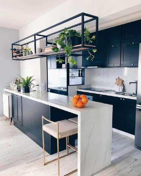 36. Prateleira aramada suspensa para cozinha americana planejada com armáriosazul marinho e bancada branca – Foto: Pinterest