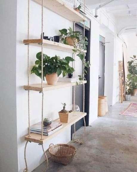 40. Prateleira suspensa com corda decorada com vasos de plantas – Foto: Fashionismo