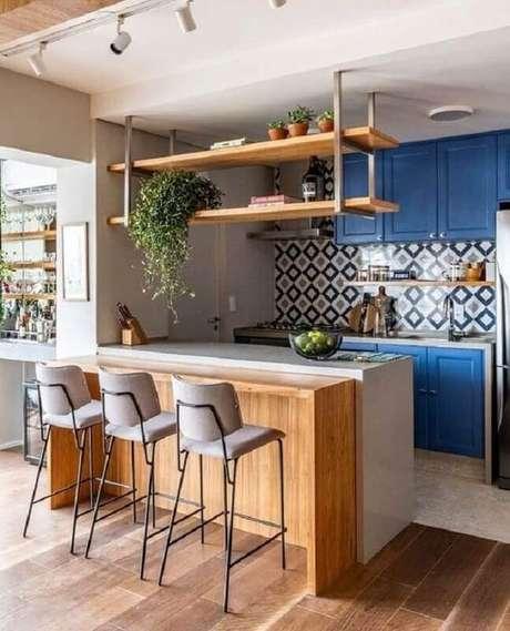 44. Prateleira suspensa cozinha planejada com armários azuis e bancada de madeira – Foto: Arkpad
