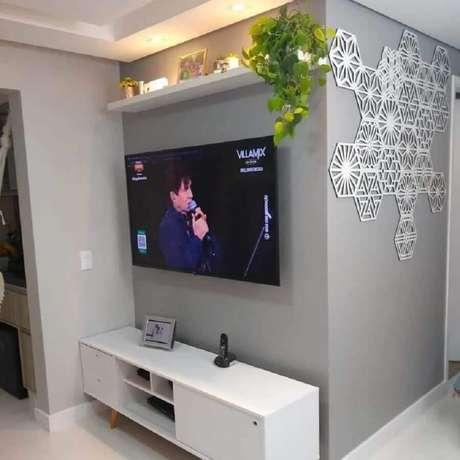 5. Prateleira suspensa para sala decorada rack branca e enfeite de parede – Foto: Pinterest