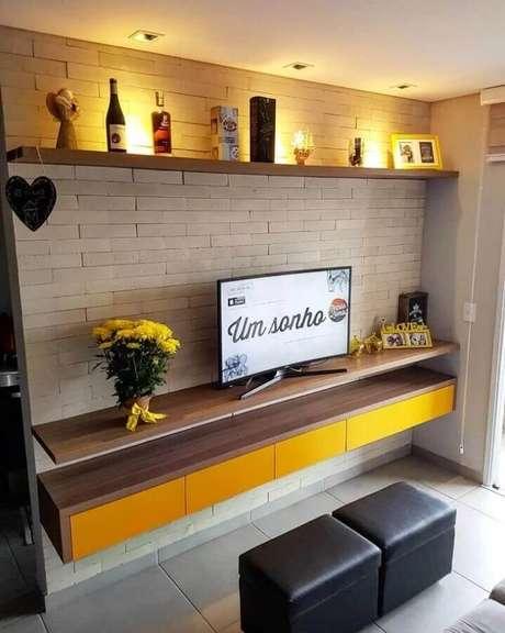 50. Prateleira suspensa para sala de TV decorada com parede de tijolinho à vista – Foto: Ap 605