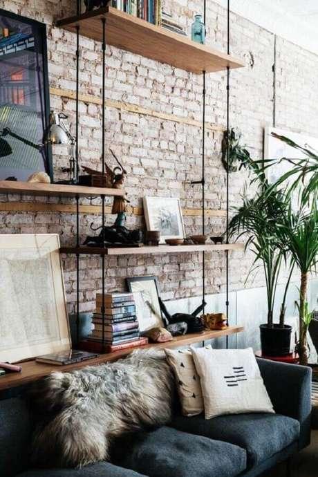 51. Prateleira suspensa teto para decoração de sala com parede de tijolinho rústica – Foto: Pinterest