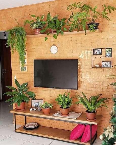 61. Sala de estar decorada com parede de tijolinho à vista e prateleira suspensa para plantas – Foto: Pinterest