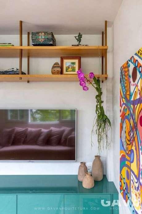 62. Sala de TV decorada com rack azul e prateleira suspensa teto – Foto: GAVA Arquitetura