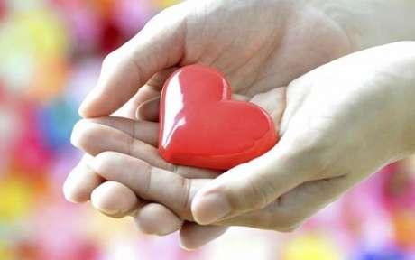 Pessoa segurando com as duas mãos um coração de plástico