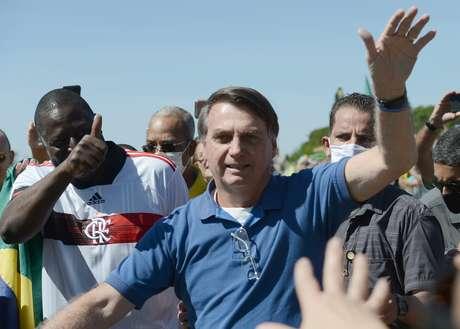 Sem máscara protetora, o presidente da República, Jair Bolsonaro, acena e cumprimenta apoiadores que participavam de um ato diante do Palácio do Planalto