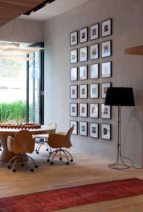 14. Decoração moderna com vários quadro de parede para sala de jantar com mesa redonda de madeira e abajur de chão preto – Foto: Pinterest