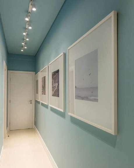 17. Corredor azul decorado com parede de quadros brancos – Foto: Pinterest