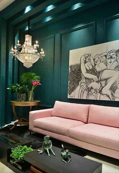 21. Decoração de sala verde sofisticada com lustre de cristal e sofá rosa – Foto: Simples Decoração