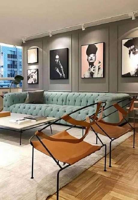 28. Decoração moderna com quadro de parede para sala de estar com sofá capitonê azul – Foto: Pinterest