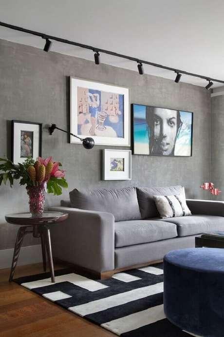 47. Quadro de parede para sala moderna com trilho de luz e parede de cimento queimado – Foto: Manual da Obra