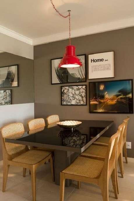 53. Quadro para parede de sala de jantar moderna com parede cinza e pendente vermelho – Foto: Muito Chique