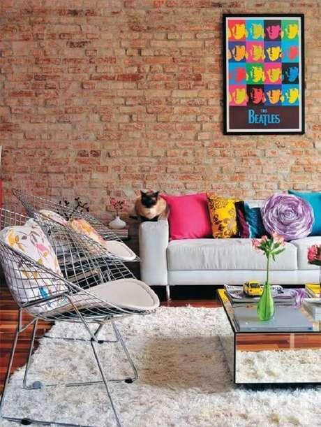 3. Quadro para parede de sala decorada com várias almofadas coloridas e parede de tijolinho – Foto: It Ideias