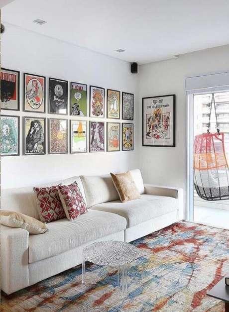 59. Os quadros de parede decorativos deram um ar jovem e descontraído para sala a sala branca com tapete colorido – Foto: Futurist Architecture