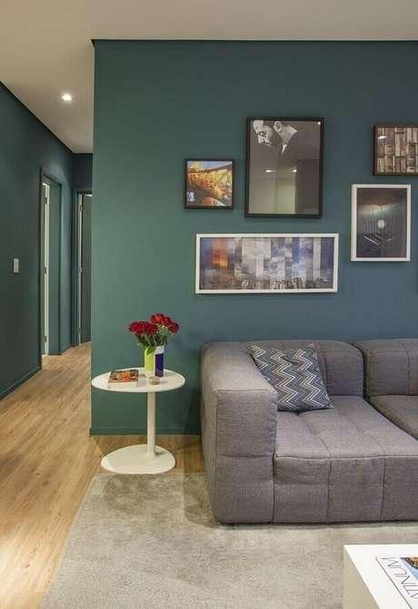 31. Quadros de parede para decoração de sala verde e cinza com mesa branca lateral – Foto: Pinterest