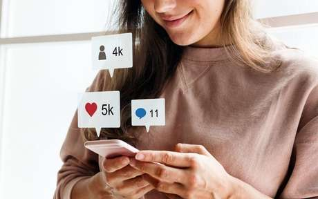 Mulher usando o celular com ilustrações de redes sociais em balões