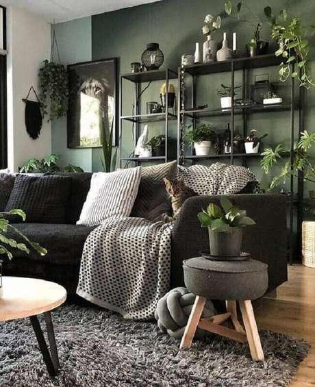 35. Decoração de sala verde escura com sofá preto e vários vasos de plantas – Foto: Homedit