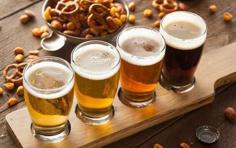 Tipos de cerveja sobre uma tábua com petisco atrás