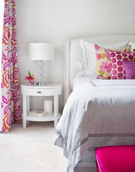 1. O criado mudo na cor branca trouxe neutralidade para o quarto com cortinas e almofadas estampadas. Fonte: Pinterest