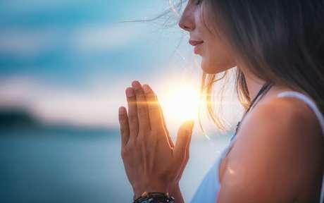 Mulher rezando com as mãos juntas e, ao fundo, um lago com pôr do Sol