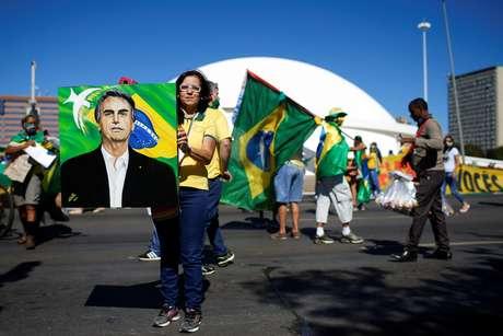 Apoiadora segura pintura com o rosto do presidente Jair Bolsonaro em manifestação em Brasília
