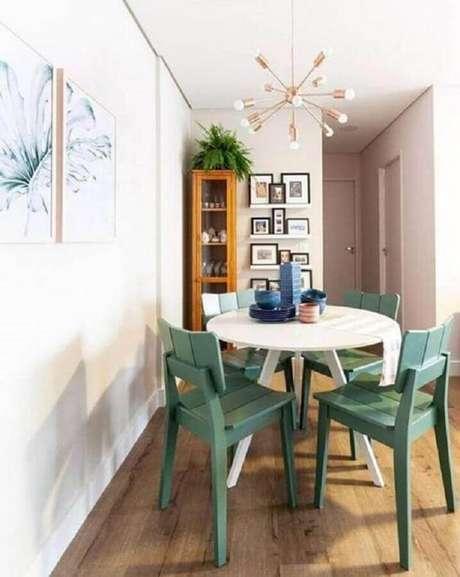 18. Sala de jantar pequena decorada com lustre moderno e cadeira verde menta para mesa redonda – Foto: Pinterest