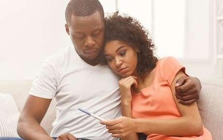 Casal olhando para um teste de gravidez